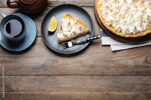 Photo Cut delicious lemon meringue pie served on wooden table, flat lay
