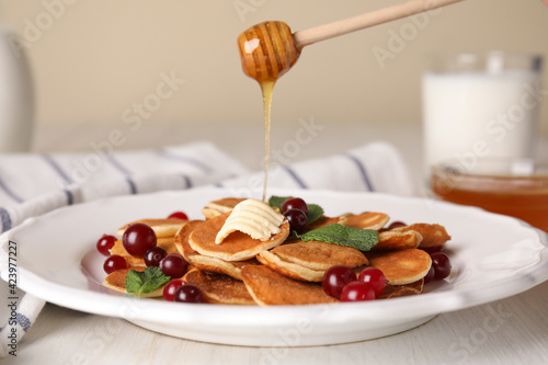 Pouring honey onto cereal pancakes with cranberries at white wooden table
