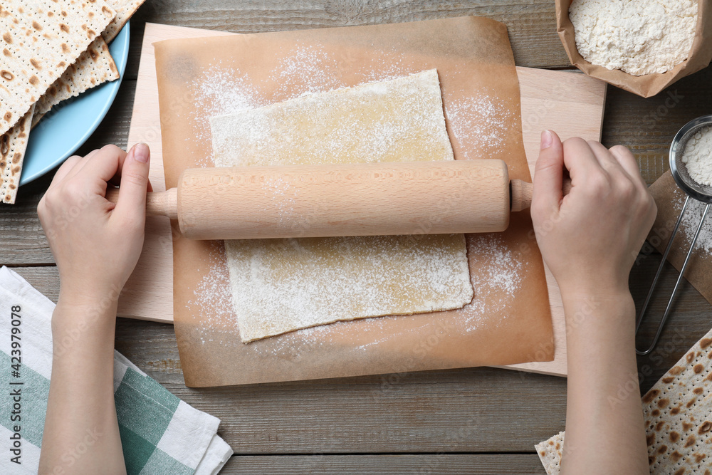 Fototapeta Woman rolling raw dough for traditional matzo at wooden table, top view