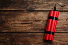 Red Explosive Dynamite Bomb On Wooden Background, Top View. Space For Text