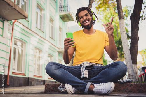 Fototapeta Photo portrait of guy sitting on the ground enjoying music with cellphone smiling on city street in summer obraz na płótnie