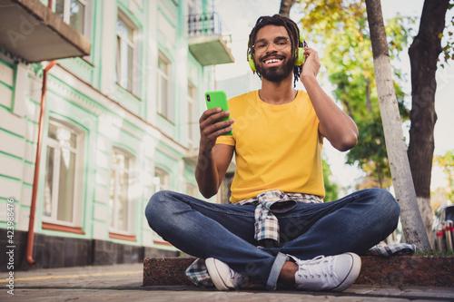 Fototapeta Photo portrait of guy sitting on the ground using smartphone in spectacles drinking beverage listening music headphones obraz na płótnie