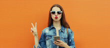 Portrait Close Up Of Young Woman With Smartphone Wearing A Denim Jacket Posing On An Orange Background