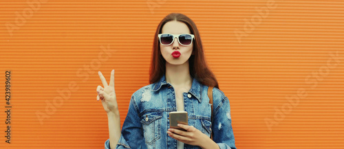 Obraz Portrait close up of young woman with smartphone wearing a denim jacket posing on an orange background - fototapety do salonu