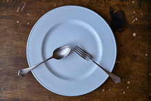 Empty White Plate With A Fork And Spoon On A Wooden Table. High Quality Photo