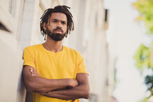 Photo Portrait Of Confident Serious Man With Dreadlocks Standing On Street With Crossed Hands Wearing Casual Clothes