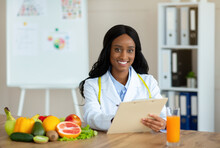 Positive Black Nutritionist With Clipboard Creating Healthy Meal Plan For Patient At Clinic, Blank Space