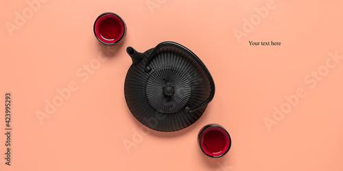 Fototapeta A minimalist Asian tea ceremony. Black metal teapot with ceramic cups on a pastel pink background. Creative layout. Top view. obraz na płótnie
