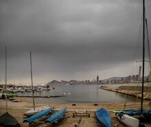 Cala En La Playa Con Barcos Delante, Mar Y Edificios Turisticos Al Fondo. Cielo Que Amenaza Lluvia