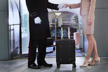 A Uniformed Doorman Helps A Woman Into The Hotel. A Trolley With Luggage. Business Woman On A Business Trip. Holiday Season.Unrecognizable Faces.
