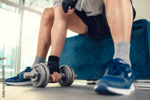 Fototapeta Young man doing exercises biceps with dumbbell on yoga mat in living room at home