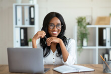Portrait Of Cheerful Black Business Lady Sitting At Her Desk With Laptop, Smiling At Camera In Office