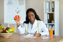 Attractive African American Nutrition Adviser Holding Grapefruit, Making Meal Plan For Client At Weight Loss Clinic