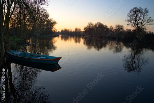 Obraz na plátně Lever de soleil sur le Loir avec présence d'une barque bleu au premier plan