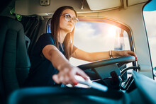 Portrait Of Beautiful Young Woman Professional Truck Driver Sitting And Driving Big Truck. She Is Dangerously Trying To Take Smart Phone While Driving.