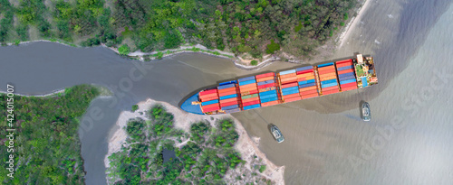 Fotografie, Obraz Canal blocked by huge cargo container ship; Aerial top view of accident container ship with salvage crews across the canal concept accident safety and insurance