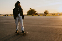 Woman Looking Away While Standing On Skateboard In Park During Sunset