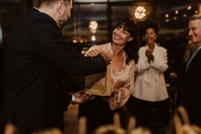 Businessman Giving Gift To Female Colleague During Office Party
