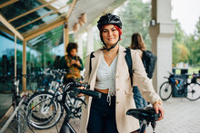 Portrait Of Female Student With Bicycle At University Campus
