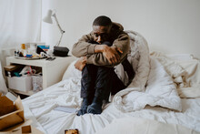 Depressed Man Sitting On Bed At Home