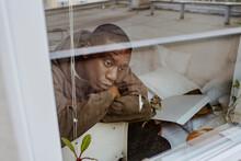 Depressed Man Sitting At Home Seen Through Window
