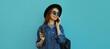 Leinwandbild Motiv Portrait close up of smiling young woman calling on a phone wearing a black round hat, denim jacket on a blue background