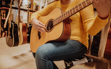 Young Woman Trying And Buying A New Wooden Guitar In Musical Instrumental Shop Or Store
