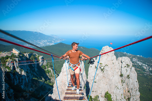 Man crossing the chasm on the rope bridge Fototapet