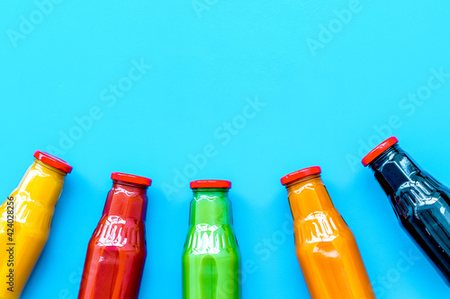 fresh organic juices in bottles for detox diet on blue background top view mock-up