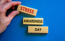 Stress Awareness Day Symbol. Wooden Blocks With Words 'Stress Awareness Day'. Beautiful Blue Background. Doctor Hand. Psychological, Business And Stress Awareness Day Concept. Copy Space.