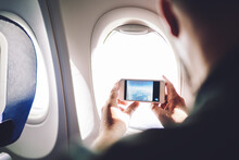 Man Taking Picture Through Airplane Window Of Scene Outside