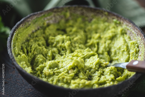 Mashed avocado in a bowl. Vegan food - fototapety na wymiar