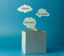 Phrase - Think Outside The Box. Box And Clouds Or Thoughts Made Of Paper On A Blue Background. Concept To Think Imaginatively Using New Ideas Instead Of Traditional Ideas.