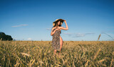An attractive sensual woman in a hat stands in wheat field and enjoys a beautiful summer day