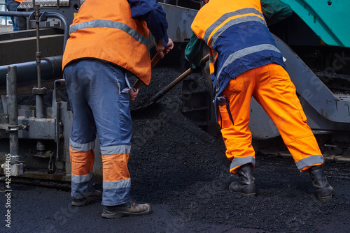 Obraz Road surface repair. Workers are laying asphalt on the road - fototapety do salonu