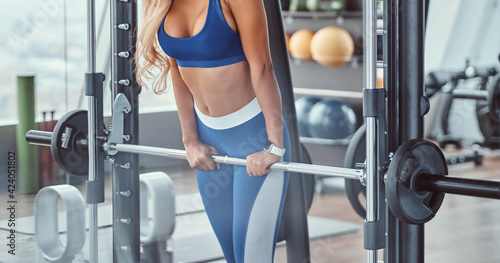 Leinwand Poster Sexy girl wearing sportswear is posing next smith machine in the fitness center