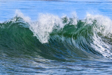 Green Ocean Wave  Off California Coast, Curling As It Moves Towards Shore. Topped With White Foam And Spray. Calm Blue Ocean In Background.