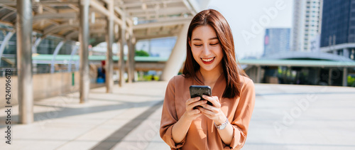 Beautiful young Asian woman in formal clothing standing outside office building using smartphone while browsing internet during break
