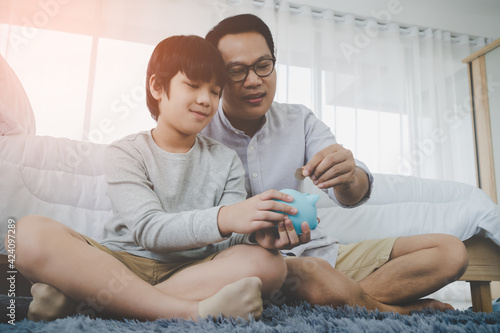 Foto Asian Father is teaching his son in money saving by inserting coin into a blue piggy bank for Financial Education concept