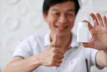 Close Up Shot Of Red Pills Vitamin Food Supplement In Small Glass Bottle With Wood Cap Was Hold By Asian Old Middle Aged Male Wears White Shirt Shows Thumb Up Smiling Happily In Blurred Background