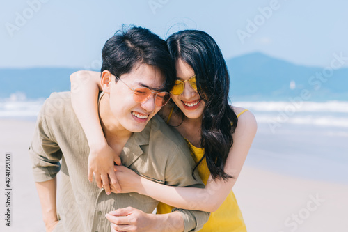 Canvas Print Young Asian couple enjoying summer vacation on the beach