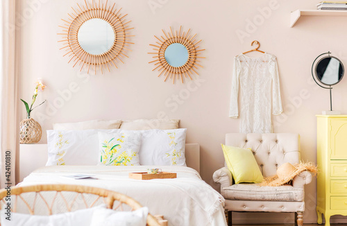 Fototapeta Beautiful, cozy modern bedroom with a large bed, chest of drawers, an armchair and decorative elements, decorated in light colors obraz