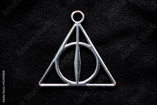Photo Front Deathly Hallows necklace on a black background of fabric texture