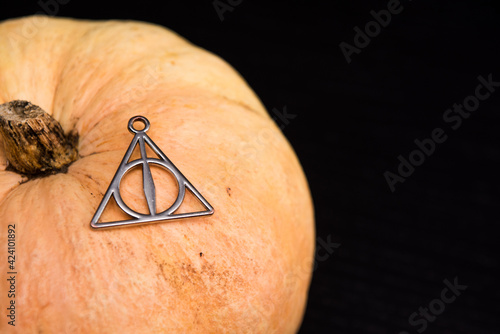 Necklace of deathly hallows on pumpkin with copy space for text. Fototapete