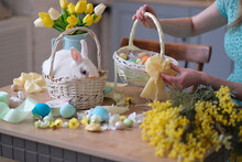 Young Woman Decorates Easter Basket In Cozy Kitchen Interior. Table Kitchen With Flowers, Easter Colorful Eggs, Presents, Pet White Rabbit Sitting In A Basket.