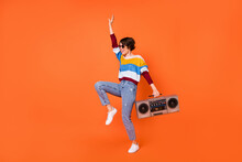 Full Length Portrait Of Cheerful Cool Girl Arm Holding Recorder Enjoy Dance Isolated On Orange Color Background
