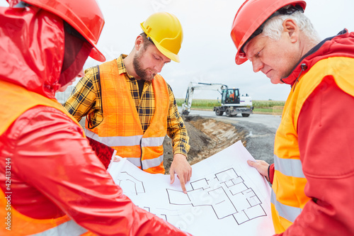 Obraz Construction workers discuss blueprint of house building - fototapety do salonu