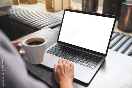 Obraz Mockup image of a woman using and touching on laptop touchpad with blank white desktop screen while drinking coffee - fototapety do salonu