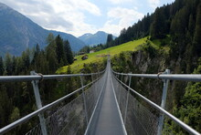 High Suspension Bridge Between Mountains Trees And Rocks