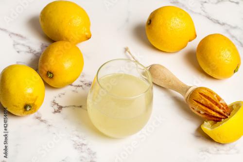 Vaso con zumo de limón natural recien exprimido sobre un fondo de mármol. Vista superior